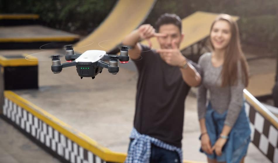 Boy and girl taking a selfie with a drone