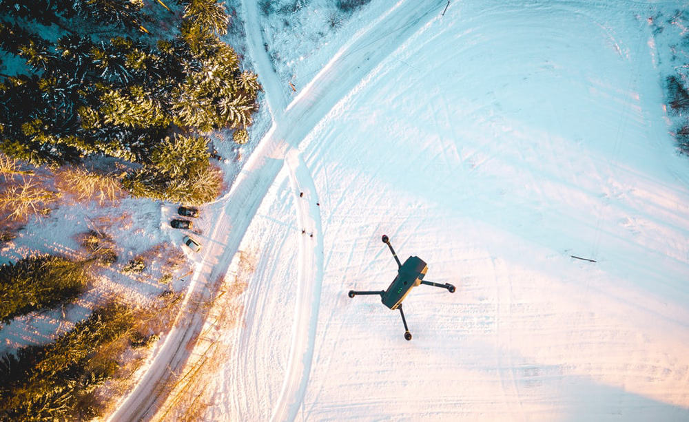 DJI Mavic Drone Flying Over Snow Covered Trees